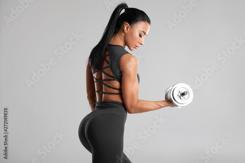 Foto auf AluDibond Fitness Fitness woman doing exercise for biceps on gray background. Muscular woman workout with dumbbells