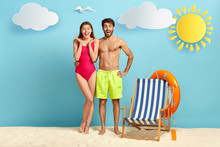 Joyful Couple Pose On Sandy Beach During Weekend. Happy Man Embraces Girlfriend, Has Naked Torso, Chill On Sea Resort, Empty Sun Chair, Stand At Tropical Island. People, Happiness, Relaxation Concept