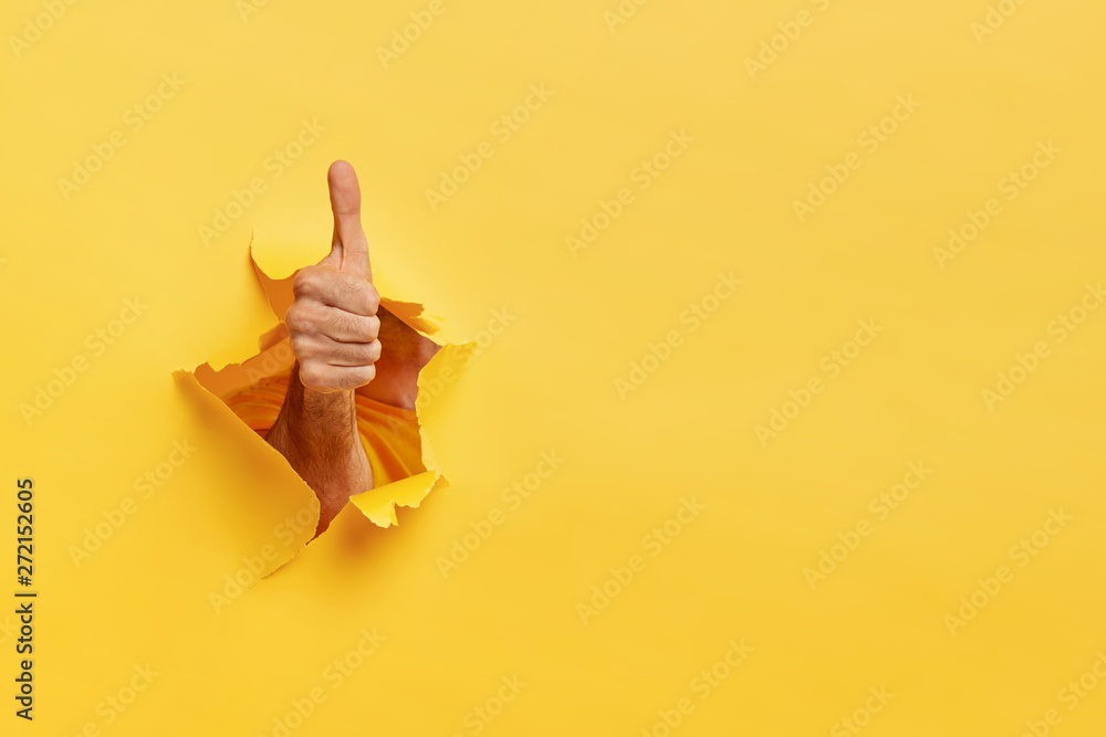 Fototapety, obrazy: Unrecognizable man shows like gesture through torn yellow wall, keeps thumb up, says you are best, demonstrates approval sign, recommends something. Copy space aside for your advertising content