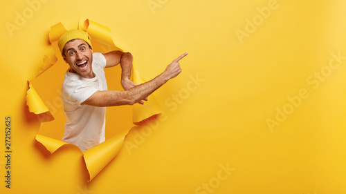 Fotografiet  Confident happy man in casual white t shirt, points at upper right corner, invit