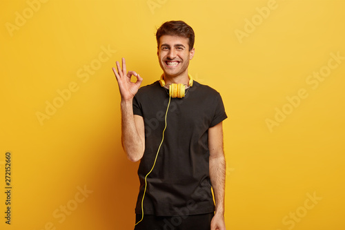 Happy Caucasian guy shows okay gesture, agrees with something, asserts everything is fine, smiles broadly, wears headphones on neck, enjoys leisure time, isolated over yellow background Canvas Print