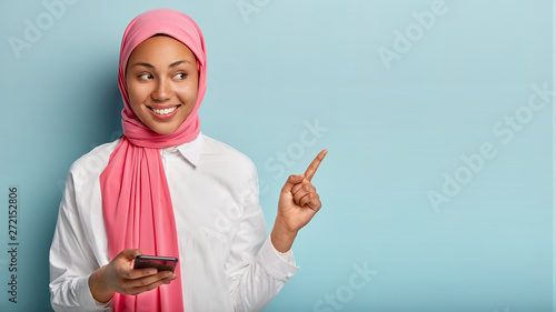 Foto Joyful pleasant looking young Muslim woman with dark skin points at upper right corner, holds smartphone device, shows free space for your advertising content, wears pink hijab, white shirt