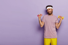 Young Man Looks Unwillingly, Holds Dumbbells In Both Hands, Has No Desire For Training, Dresses In Active Wear, Stands Against Purple Background With Copy Space For Your Advertising Content.