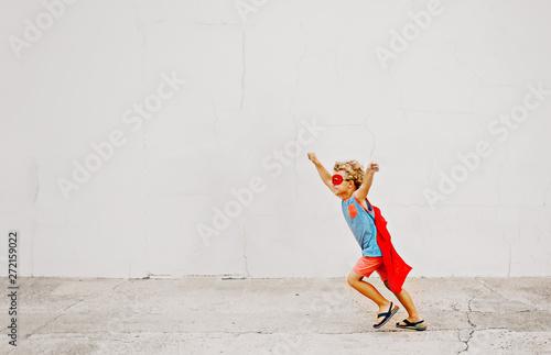 Fotografia Little boy wearing cape dressed up like a superhero