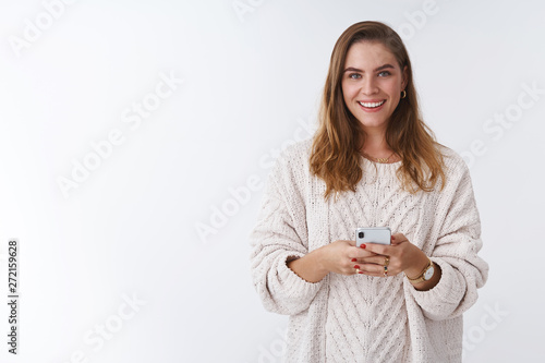Studio shot charming happy smiling woman holding smartphone