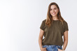Leinwanddruck Bild - Attractive modern young urban woman chestnut short haircut wearing olive t-shirt holding hands pockets smiling friendly relaxed sound-minded pose, outgoing woman communicating grinning