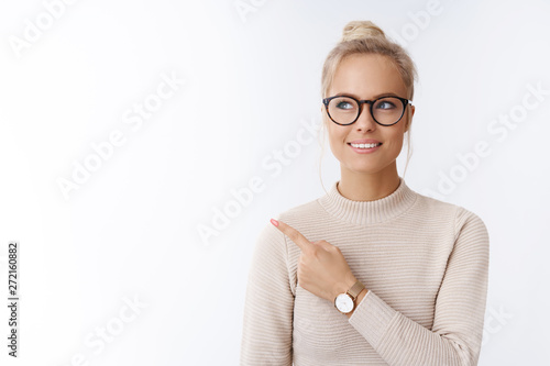 Obraz Closed-up shot of beautiful caucasian blond woman in glasses and sweater feeling creative and productive pointing at upper left corner smiling dreaming, thinking against white background - fototapety do salonu