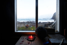 Look Through The Window Of A Cabin At The Coast With A Burning Candle In The Foreground.
