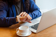 Close up portrait of young adult man freelancer in casual style sitting in cafe with laptop and cup of coffee, looking to the watch to check the time, bussinessman in office. Indoor, lifestyle concept