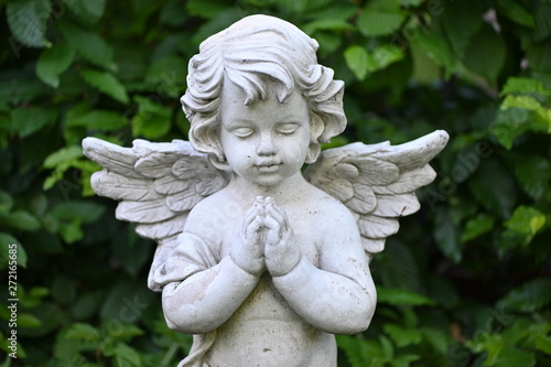 A white sandstone sculpture of a praying angel. Fototapet