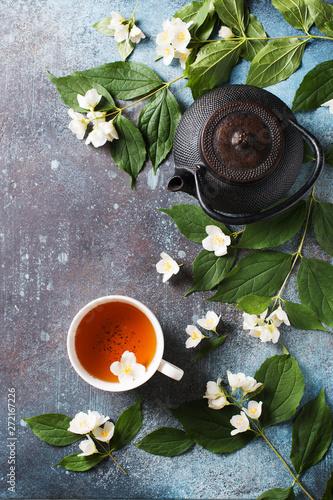 Fotografie, Tablou Tea jasmine background with teapot, leaves and flowers on dark texture