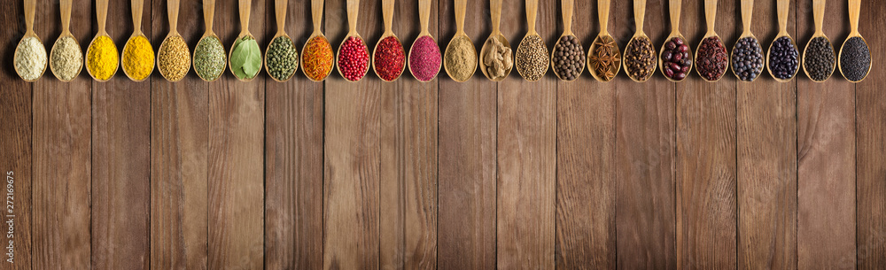 Fototapety, obrazy: Spices and herbs on wooden table as background for design of packing with food. Collection of spices in spoons with empty space.