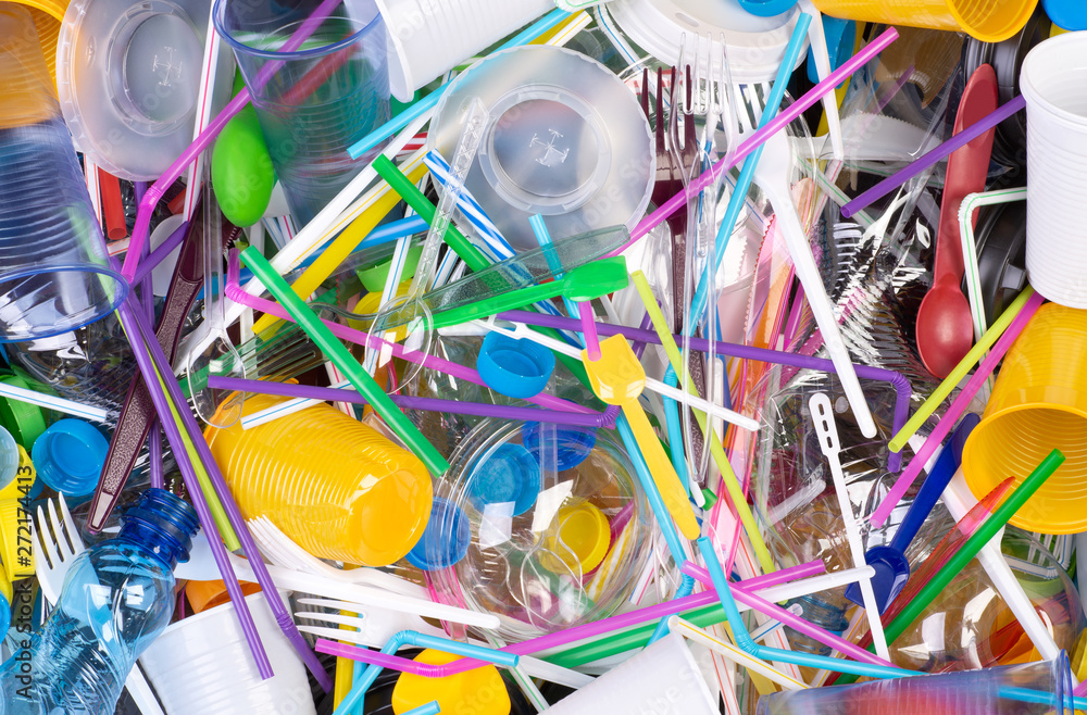 Fototapeta Disposable single use plastic objects such as bottles, cups, forks, spoons and drinking straws that cause pollution of the environment, especially oceans. Top view.