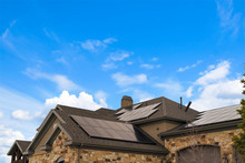 Cloudy Blue Sky Over A Home With Solar Panels On The Pitched Roof