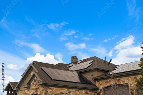 Obraz Cloudy blue sky over a home with solar panels on the pitched roof - fototapety do salonu