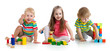 Cute little children playing with toys or blocks and having fun while sitting on floor isolated over white background
