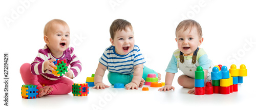 Obraz Nursery babies toddlers playing with color toys isolated on white background - fototapety do salonu