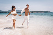 Young Beautiful Man And Woman Couple In White Clothes Running Along The Beach. Couple Man And Woman In The Rays Of The Sun On The Ocean Bank.