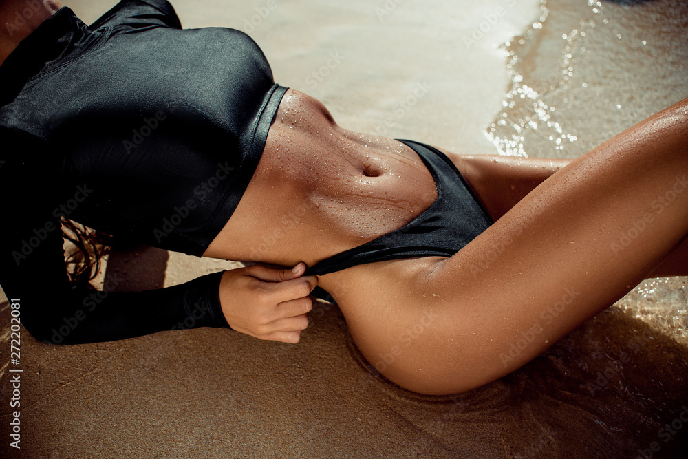 Fototapety, obrazy: Close up photo of young woman in black swimsuit sunbathing on white sand. Fashion girl tanning on tropical beach. Close up of beautiful slim body of tanned woman lying on side.