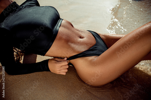 Close up photo of young woman in black swimsuit sunbathing on white sand. Fashion girl tanning on tropical beach. Close up of beautiful slim body of tanned woman lying on side.