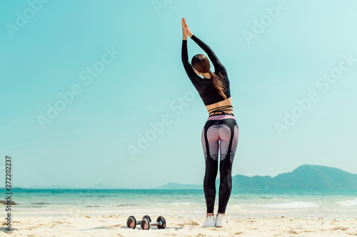 Tuinposter School de yoga Beautiful woman practices yoga by the sea on a sunny day. The woman does stretching exercises. Dumbbells lying on the sand. Back view