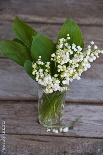 Wall Murals Spring bouquet of lilies of the valley on woden background.
