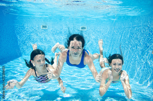 Photo  Family swims in pool underwater, happy active mother and children have fun under