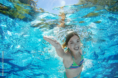 Child swims underwater in swimming pool, happy active teenager girl dives and ha Canvas Print
