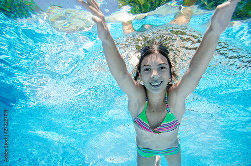 Photo  Child swims underwater in swimming pool, happy active teenager girl dives and ha