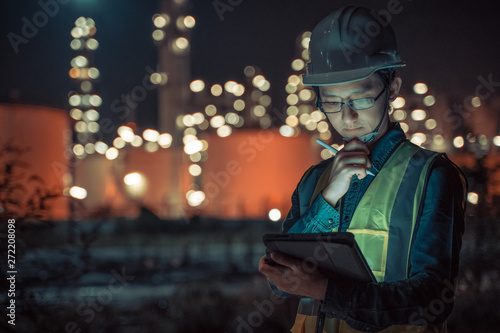 Fototapeta Engineer Petrochemical Asian man work late and hard with Smart tablet Inside the Refinery oil and gas Industry Factory at night obraz