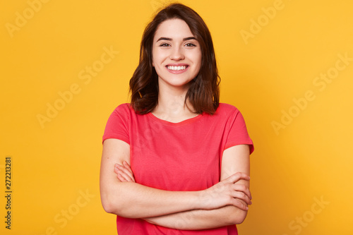 Fotografía  Indoor shot of magnetic beautiful young girl standing with folded arms, looking directly at camera, having sincere smile on her face, posing straight isolated over yellow background in studio