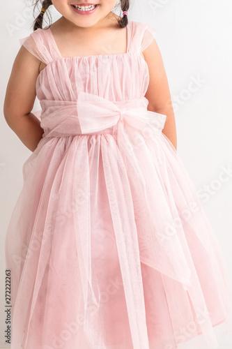 Fotografering  白背景にピンクのキッズドレスを着た女の子が座っているプリンセスお姫様