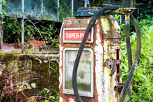 Rotting And Rusty Old Gas Fuel Petrol Pump Abandoned In An Overgrown Yard Beside A Derelict Building