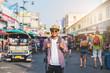 Young asian traveller man walking in Khaosan Road walking street in bangkok thailand on vacation time.