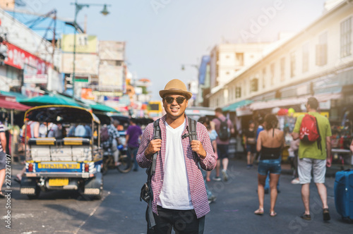 Young asian traveller man walking in Khaosan Road walking street in bangkok thailand on vacation time Canvas Print