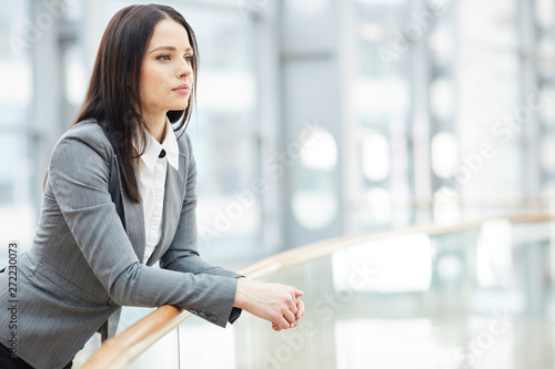 Fotografía  Serious beautiful young business lady in blouse and gray jacket leaning on raili