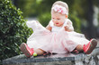 Leinwandbild Motiv Little baby girl fashionista in the park. Smiling child outdoors. Baby looking at her dress. Cute child closeup portrait.