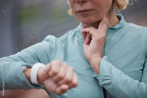 Photo sur Toile Les Textures Mature sportswoman checking her pulse while keeping two fingers under neck and looking at wristwatch after workout