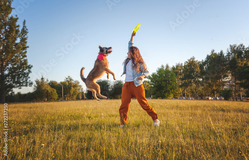 Fotografie, Obraz  Young beautiful curly girl playing with her dog with a  frisbee in summer park