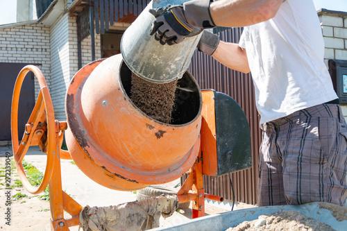 Fotografie, Obraz builder working with shovel during concrete cement solution mortar preparation