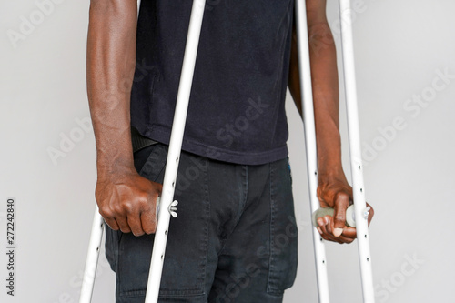 Photo African man on crutches on a gray background