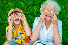 Happy Grandmother And Grandchild Fooling Around The Lawn Of Putting Chamomiles Instead Of Eyes. Family Love And Relationships. Family Happy Holiday.