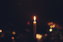 Candles Burning At Night. White Candles Burning In The Dark With Focus On Single Candle In Foreground.