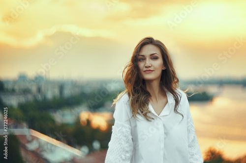 obraz PCV Young woman over cityscape golden sunset