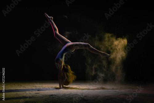 Stampa su Tela  Female dancer doing handstand under colorful light