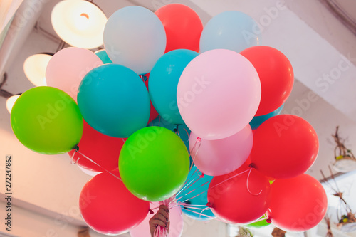 Hand holding Colorful balloons on the mint background.
