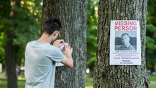 A Young Man Puts Up Ads For A Missing Person In The Park