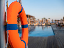 Orange Lifebuoy Near Public Swimming Pool On A Blurred Background, A Swimming Pool Is Visible
