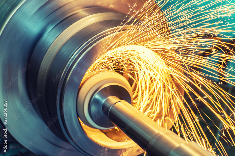 Fototapety, obrazy: Internal grinding of a cylindrical part with an abrasive wheel on a machine, sparks fly in different directions. Metal machining.