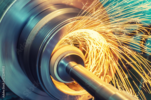 Obraz Internal grinding of a cylindrical part with an abrasive wheel on a machine, sparks fly in different directions. Metal machining. - fototapety do salonu